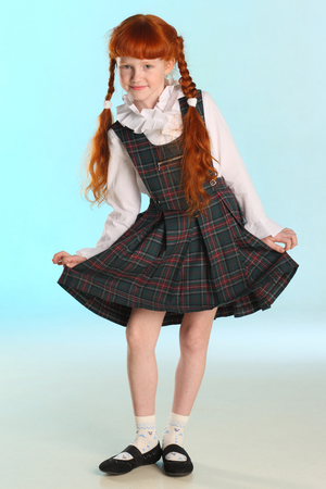 Beautiful little redhead girl shows her school uniform at full length. Elegant attractive child with a slender body and slim bare legs. The young schoolgirl is 8 years old.