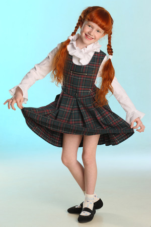 Beautiful happy little redhead girl shows her school uniform at full length. Elegant attractive child with a slender body and slim bare legs. The young schoolgirl is 8 years old. Foto de archivo