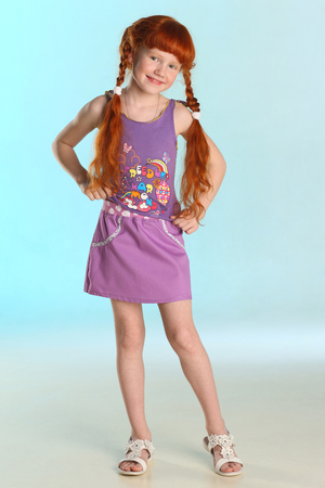 Beautiful charming little redhead girl shows her summer clothes at full length. Happy attractive child with a slender body and slim bare legs. The young pre-teen girl 8 years old.
