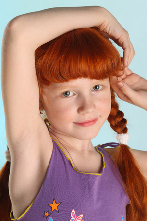 Close-up portrait of beautiful charming little redhead girl. Happy attractive child posing in a summer clothes. The pre-teen fashion model 8 years old. Stock Photo