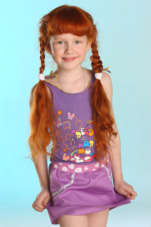 Portrait of beautiful charming little redhead girl. She shows her summer clothes. Happy attractive child with a slender body and slim legs. The young pre-teen model 8 years old.