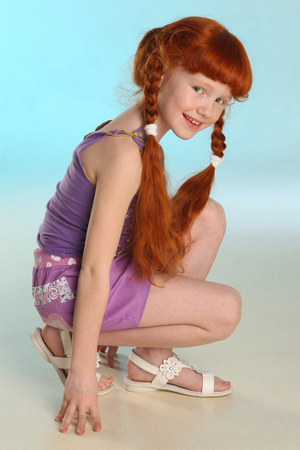 Beautiful charming little redhead girl demonstrates her summer clothes squatting. Happy attractive child with a slender body and slim bare legs. Fashion pre-teen model 8 years old.