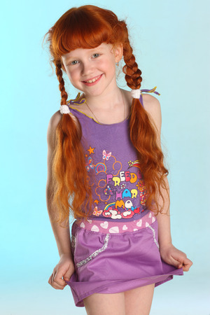 Portrait of beautiful charming little redhead girl. She shows her summer clothes. Happy attractive child with a slender body and slim bare legs. The young pre-teen model 8 years old.