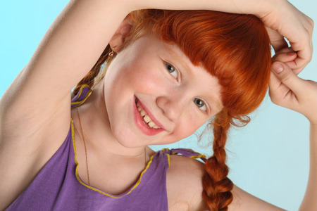 Close-up portrait of beautiful charming little redhead girl. Happy attractive child posing in a summer clothes. The pre-teen fashion model 8 years old. Stockfoto
