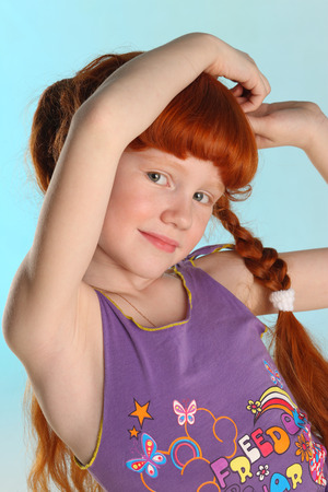 Close-up portrait of beautiful charming little redhead girl. Happy attractive child posing in a summer clothes. The pre-teen fashion model 8 years old. Фото со стока