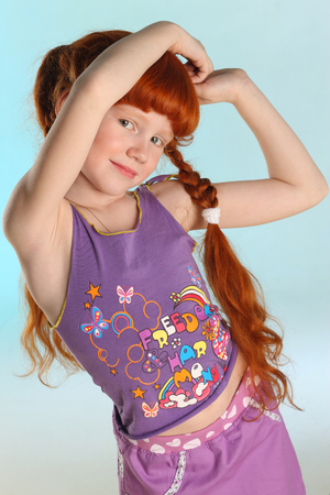 Portrait of beautiful charming little redhead girl. She shows her summer clothes. Happy attractive child with a slender body and nice bare belly. The young pre-teen model 8 years old.