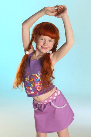 Portrait de la belle petite fille rousse charmante. Elle montre ses vêtements d'été. Heureux enfant attrayant avec un corps mince et un joli ventre. Le jeune mannequin pré-ado de 8 ans. Banque d'images - 101796538