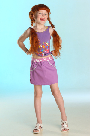 Beautiful charming little redhead girl shows her summer clothes at full length. Happy attractive child with a slender body and slim bare legs. The young pre-teen girl 8 years old. Stockfoto - 101796541