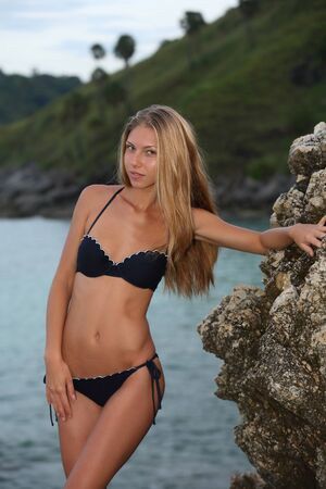 Gorgeous young blonde adult girl with her slender tanned body is standing on a rocky seashore against the evening light blue water and posing in her dark bikini. Reklamní fotografie