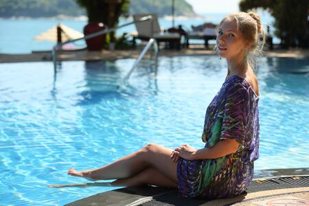 Charming attractive graceful young blond woman in a summer dress sits on the edge of the pool and lowers her long slender legs into a clean sparkling blue water Stockfoto
