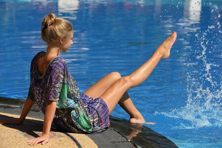 Happy adorable attractive slender young adult blonde girl sitting on the edge of the pool and splashes clear blue water by her long bare tanned legs