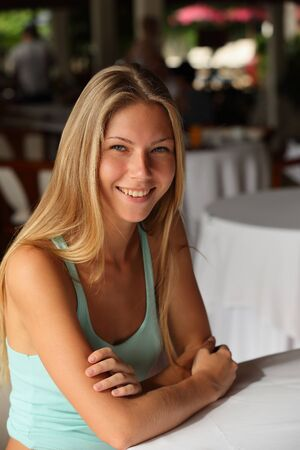 Portrait of a happy and smiling attractive young adult blonde woman with beautiful bare hands sitting at a table with a white tablecloth Stockfoto