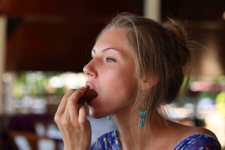 Close-up of portrait of a beautiful young blonde girl who eats a tasty piece baked from dark rye flour Stockfoto