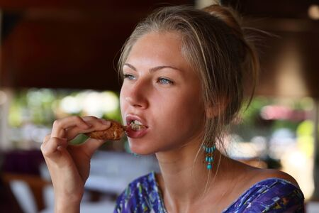 Close-up of portrait of a beautiful young blonde girl who eats a tasty piece baked from dark rye flour Фото со стока