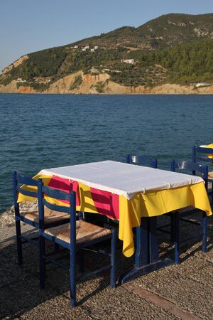 Restaurant in the open air by the sea, evening. Mediterranean Sea, South of Europe, Greece, Skopelos Island. Фото со стока