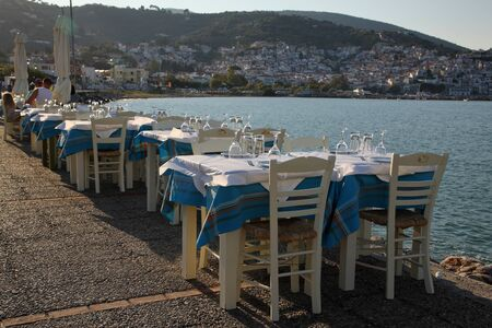Restaurant in the open air by the sea, evening. Mediterranean Sea, South of Europe, Greece, Skopelos Island. Stockfoto - 126432977