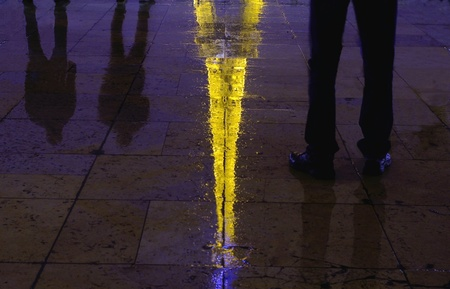 The wet surface reflections of the Eiffel Tower in Paris with the visible shadows of people staring at the tower photo