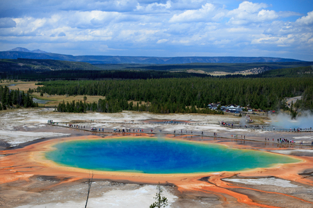 prismatic: A distant view of the Great Prismatic Spring in Yellowstone National Park with Clouds and Mountains in the background
