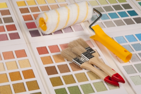 refurbishing: Brushes and a paint roller on color palette  Stock Photo