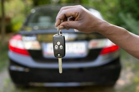 車のキーを保持している男