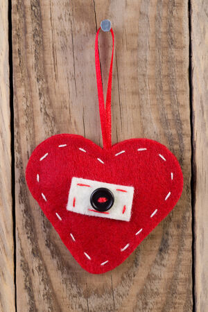 Heart decoration hanging against wooden background  photo