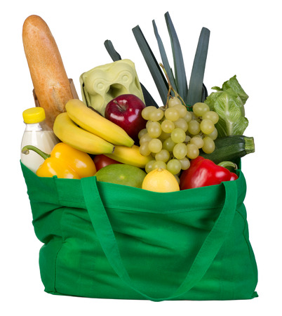 Groceries in a green bag isolated on white background  photo