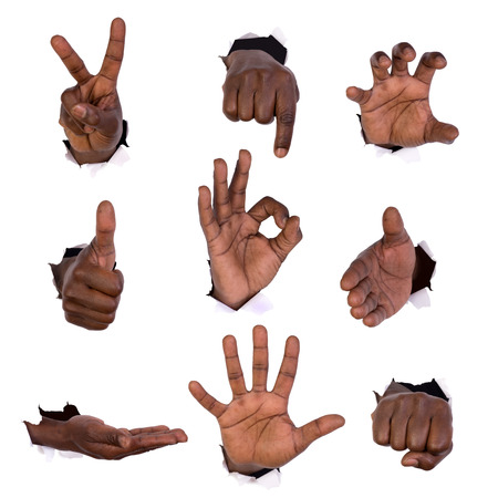 Hand gestures through holes in paper isolated on white Stock Photo