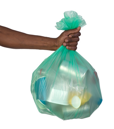 Man holding a plastic bag full of garbage, isolated on white Stockfoto