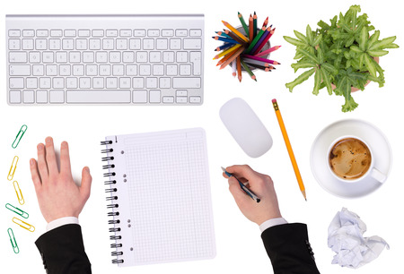 Office desktop with various objects and a businessman working photo