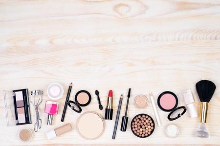 productos de belleza: cosméticos de maquillaje en blanco, fondo de madera con espacio de copia, vista desde arriba