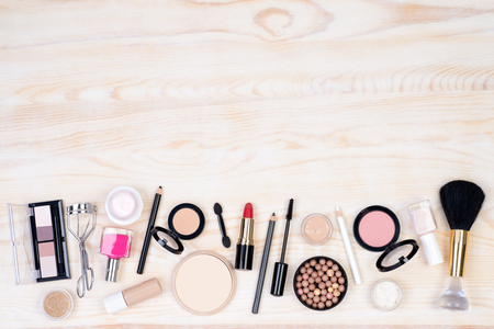 Makeup cosmetics on white, wooden background with copy space, top view