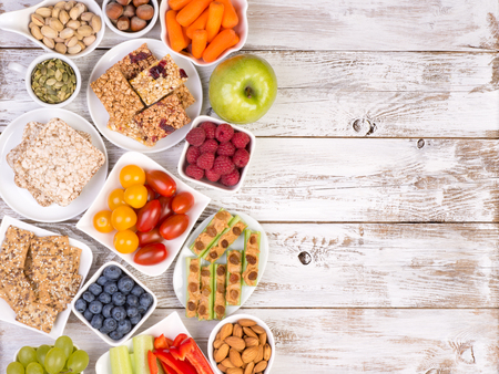 Healthy snacks on wooden table with copy space, top view