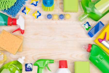Cleaning supplies on wooden background with copy space, top view