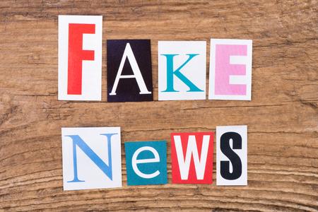 fake: Phrase Fake news on wooden background Stock Photo