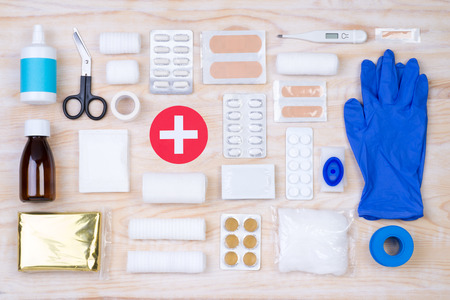 First aid kit on wooden background, top view Stock Photo