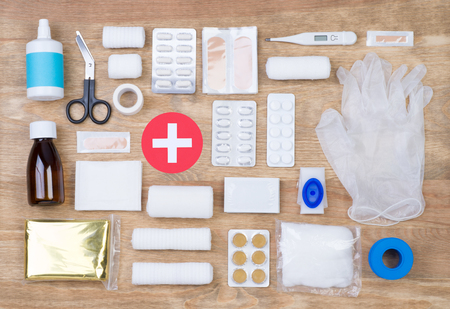 First aid kit on wooden background, top view Standard-Bild