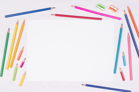 Blank piece of paper with colorful pencils on kid's desk, top view with copy space