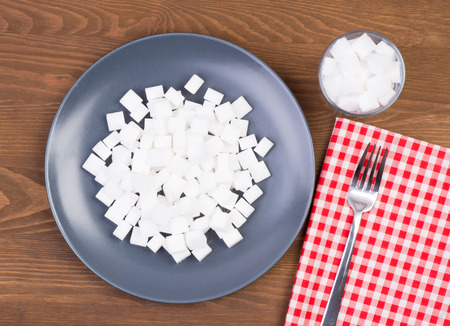 Sugar cubes on a plate and in a glass. Too much sugar in food concept