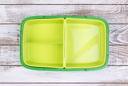 Empty lunch box on wooden table, top view