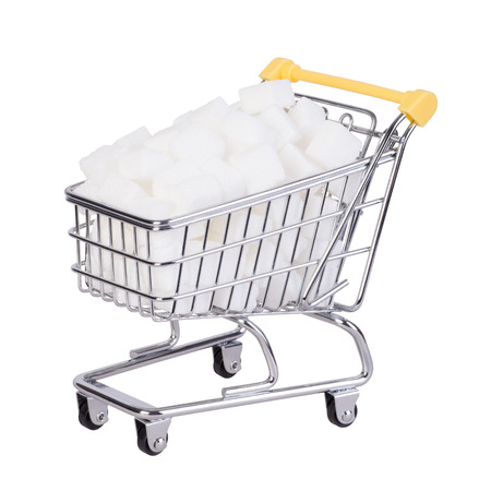 Sugar cubes in a shopping cart, isolated on white background