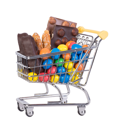 Sweets in a shopping cart isolated on white background