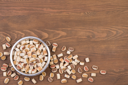 Dog food in a bowl on a wooden background with a copy space Stock Photo