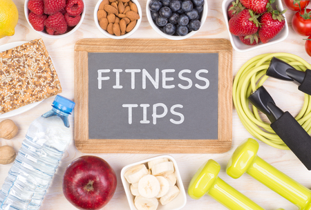 Phrase Fitness Tips written on a small blackboard among healthy food and fitness equipment Stock Photo