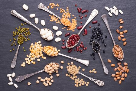 Legumes, lentils, chikpea, dry peas and beans in spoons on stone background. Top view
