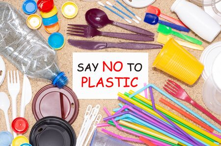 Disposable single use plastic objects such as bottles, cups, forks, spoons and drinking straws that cause pollution of the environment, especially oceans. Top view on sand Stock Photo