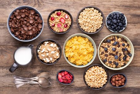 Breakfast cereals in bowls on rustic wooden table, top view