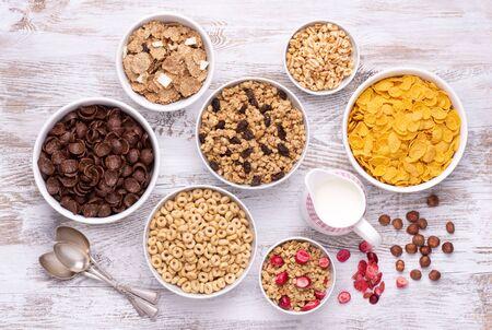 Cereali per la colazione in ciotole bianche su tavolo di legno bianco, vista dall'alto