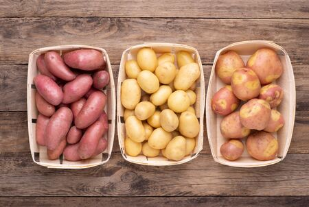 Different types of potatoes in boxes on wooden rustic table