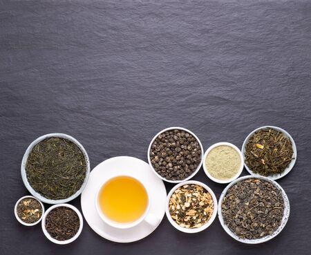 Tazza di tè verde e ciotole di varie foglie di tè essiccate su sfondo scuro, pietra, vista dall'alto con spazio copia Archivio Fotografico