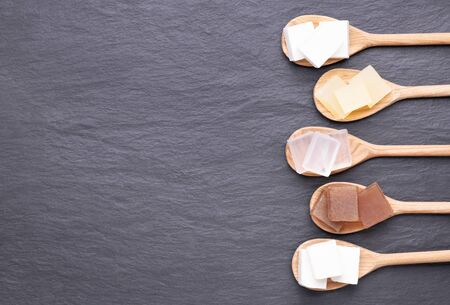 Five kinds of glycerin soap bases on wooden spoons on black stone background with copy space